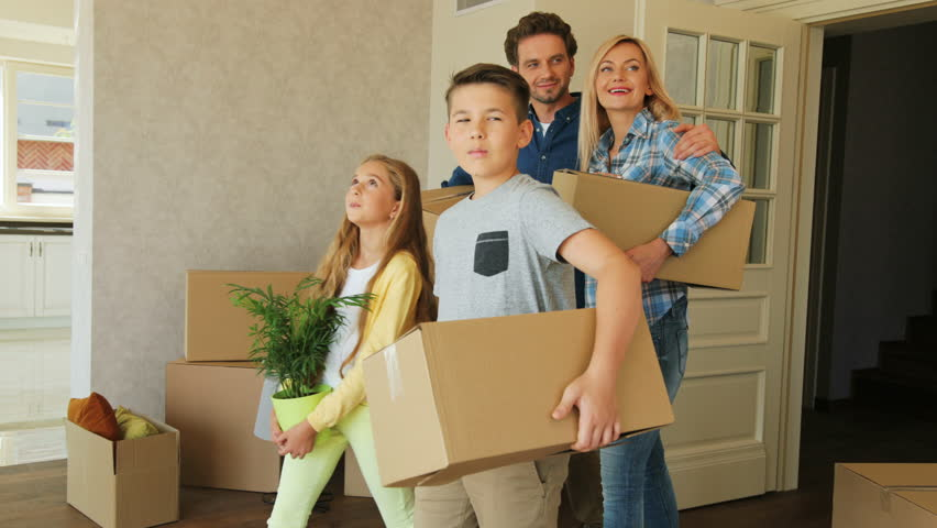 Portrait of young exaciting family carrying cardboard box into the new modern home to the living room.