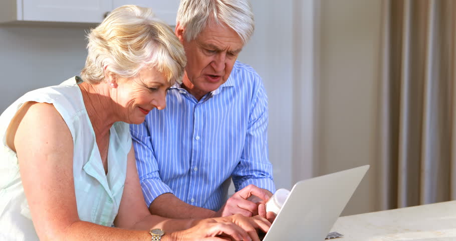 Senior Caucasian couple checking medicine while using laptop in kitchen at home | Shutterstock HD Video #29389201