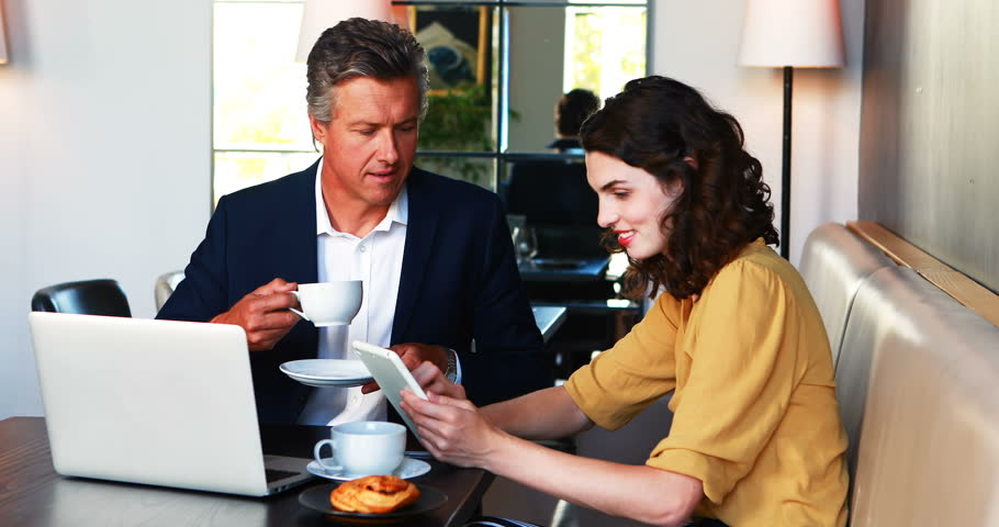 Businessman and colleague discussing over digital tablet while having coffee in restaurant   Shutterstock HD Video #29391625