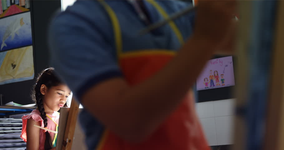 Side view of mixed race attentive schoolgirl panting on canvas in school | Shutterstock HD Video #29393308