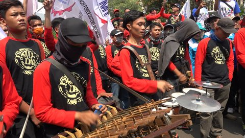 JAKARTA, INDONESIA - APRIL 2017: Labor union members play traditional music during May Day protest in Jakarta, Indonesia
