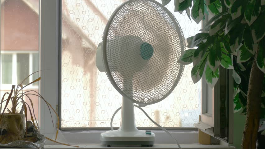 Domestic fan on window-sill in room in hot days / Household fan on windowsill in room