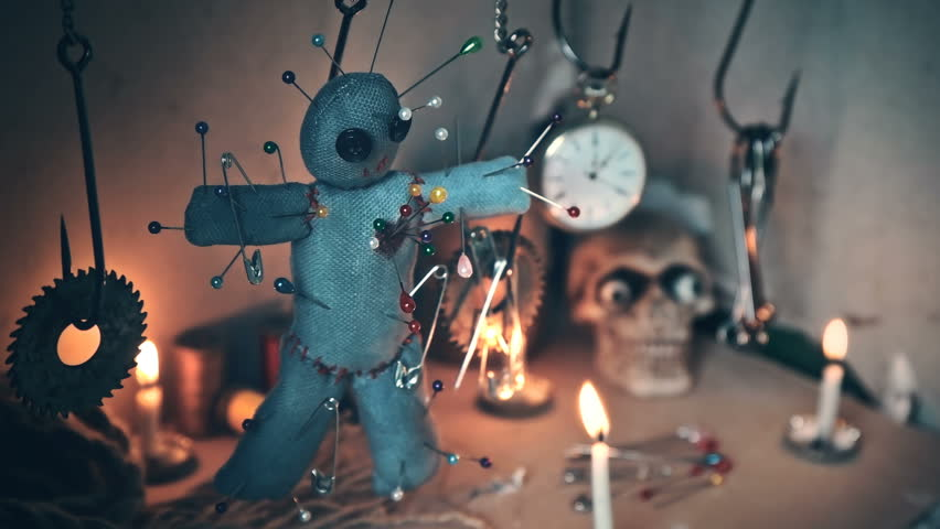The voodoo doll swinging on the hook over the ritual table