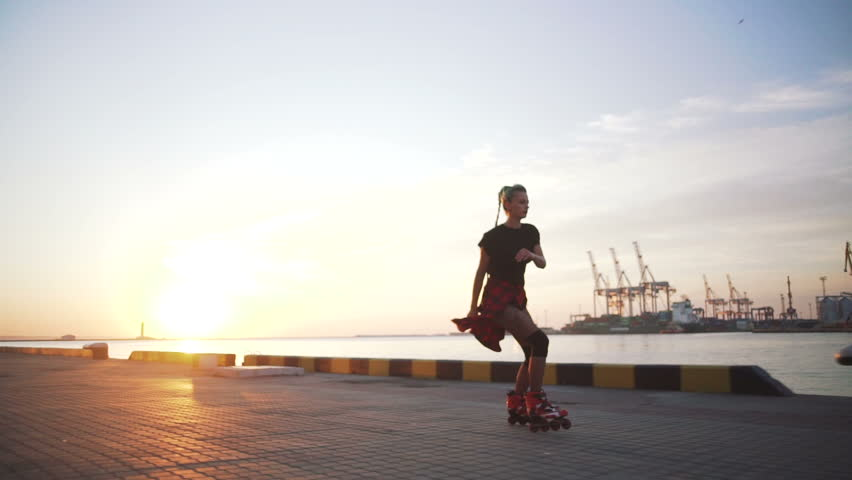 Young stylish funky girl with green hair riding roller skates and dancing near sea port during sunset, slow motion