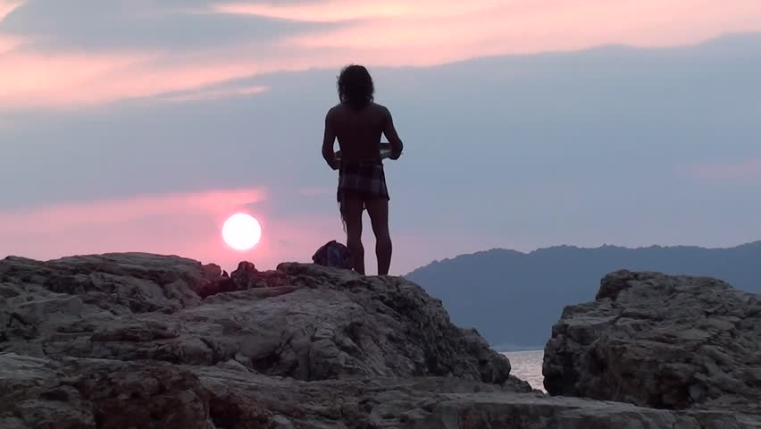 Man with tambourine praying on rock to the declining sun | Shutterstock HD Video #2944342