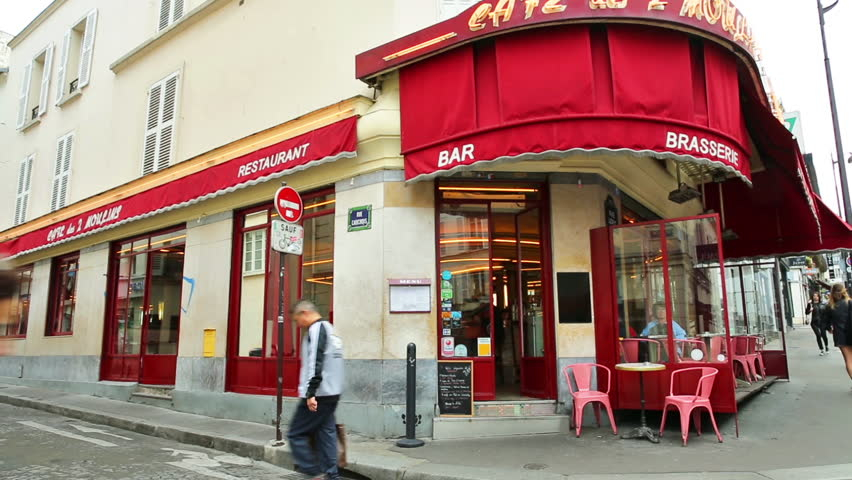 PARIS, FRANCE - JULY 3, 2017: Exterior of popular brasserie cafe deux moulins of Montmartre, location of Amelie movie on 2001. With customers enjoying their breakfast in the morning.