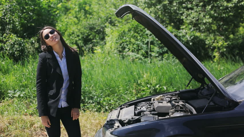Distempered attractive businesswoman on coutryside road trying to get help with her broken down car