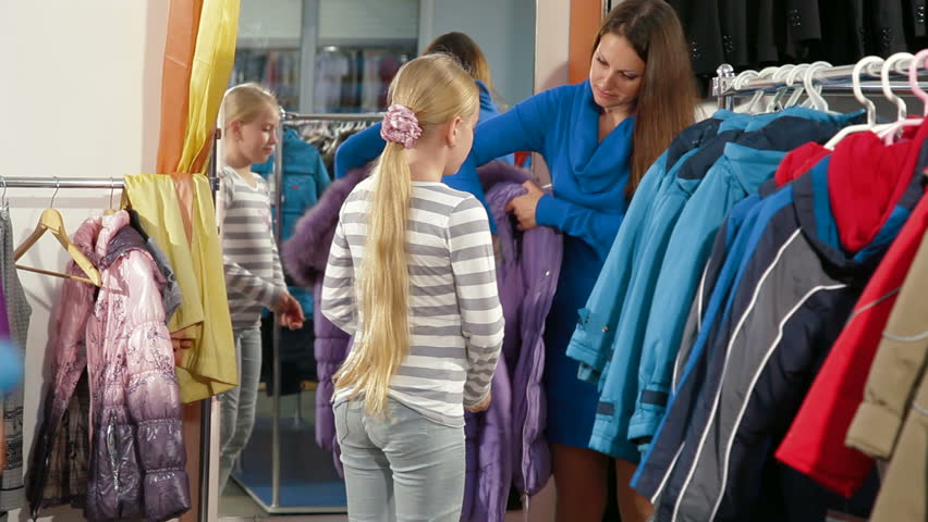 Mother with two daughters shopping for girls clothes in a clothing store, child trying on warmest jacket | Shutterstock HD Video #2946226