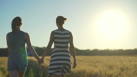 Girl couple walking holding hands Embrace wheat field sunny rapid slow motion