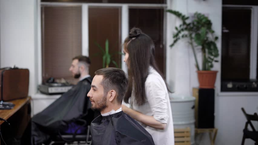 Female and male barbers are working with clients with cutting capes in the barbershop. Young woman is using hairclipper for shaving head of handsome man with her colleague in the background. #29479471