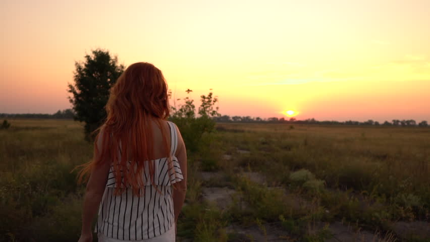 Happy red-haired woman walking in the field at sunset, turning around and looking into the camera, slow motion   Shutterstock HD Video #29481835