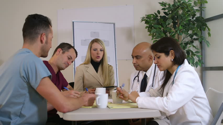 Lovely blond pharmaceutical saleswoman and group of doctors sitting at a table stops her presentation and all smile for camera.