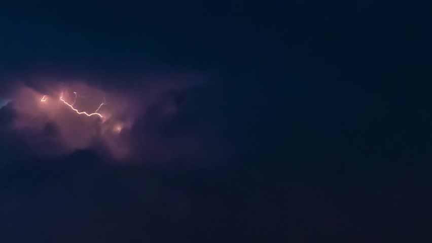 Time lapse clip of evening fluffy curly rolling clouds with lightning