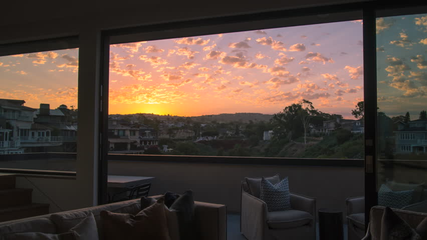 Early morning time lapse from a luxury home living room through balcony doors of a stunning yellow and gold sunrise with clouds overhead overlooking a canyon, coastal homes and mountains.