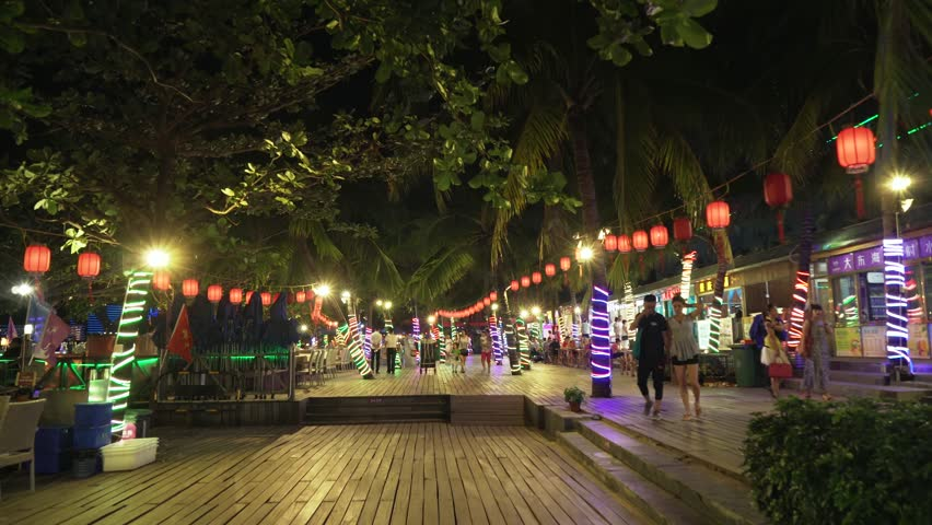 Sanya, China - April 06, 2017: Walking on a night tourist promenade with restaurants on Dadonghai beach time lapse stock footage video