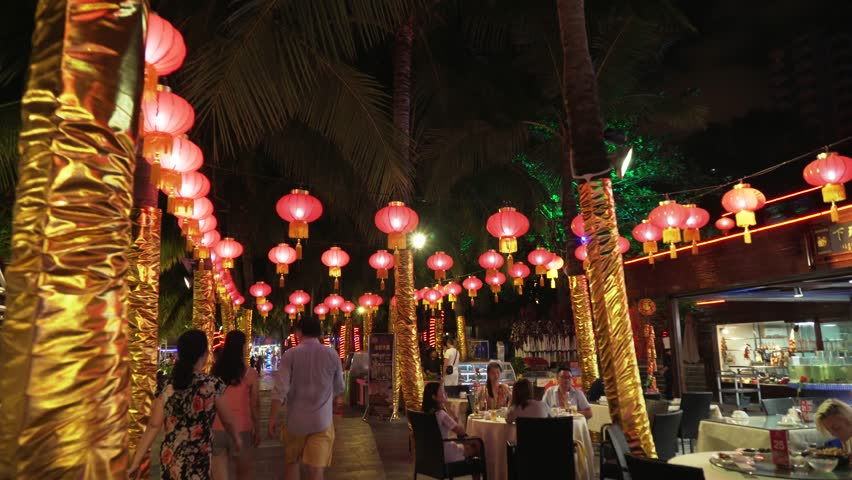 Sanya, China - April 06, 2017: Walking on a night tourist promenade with restaurants on Dadonghai beach stock footage video