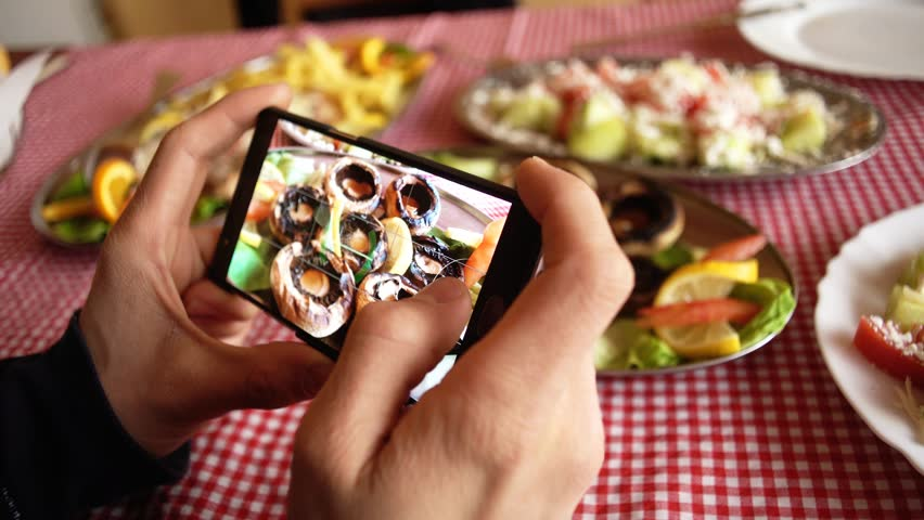 Hands of Caucasian male holding a smart phone and taking a photo of delicious food in a restaurant. #29541214