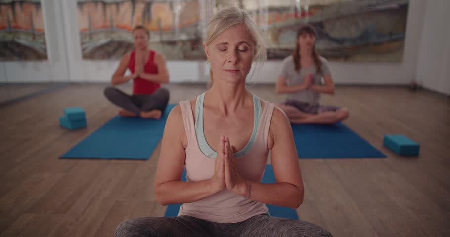 Beautiful retired woman relaxing during meditation exercise at a yoga class in a fitness studio