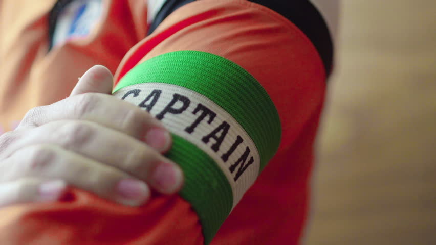 Captain puts armband on sleeve. Sports captain wears his armband with pride ahead of match, preparation before big game. Royalty-Free Stock Footage #29555482