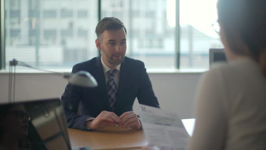 Man goes to job interview, sits and desk and is being interviewed by female boss, nervous and anxious he fiddles with a pen as she checks over his CV. Royalty-Free Stock Footage #29555491