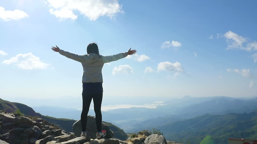 Cheering young woman hiker open arms at mountain peak | Shutterstock HD Video #29587852