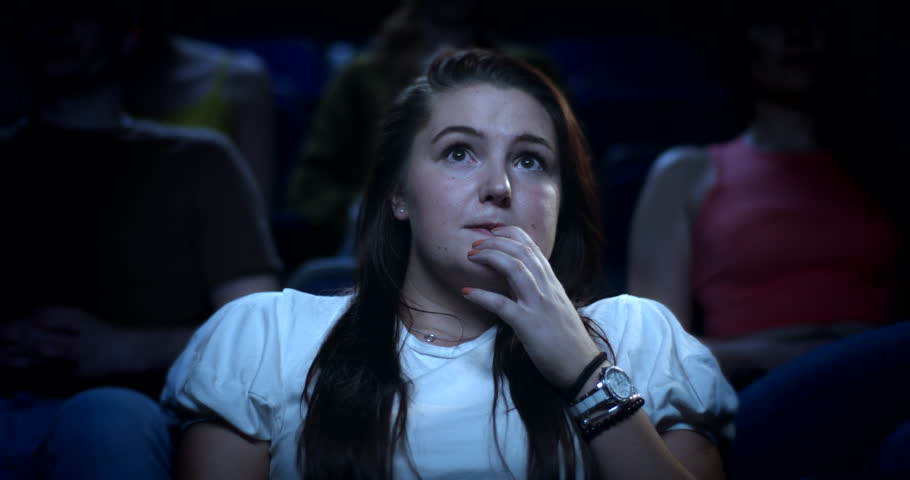 A young nervous woman at the cinema reacting to a scary movie   Shutterstock HD Video #29595364