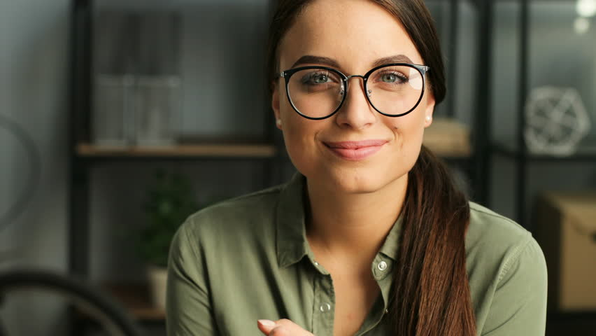 Portrait shot of attractive woman looking at the camera and smiling while working in the urban office. close up | Shutterstock HD Video #29603881