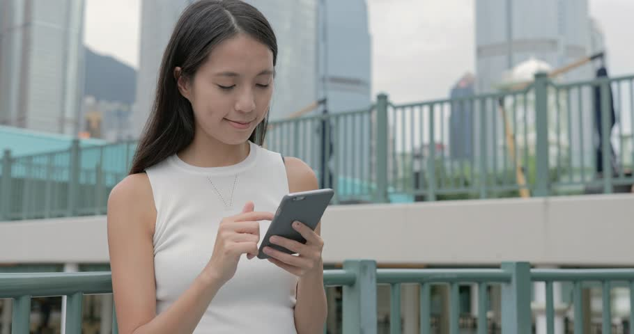 Elegant beautiful woman texting on smartphone in the city #29630401