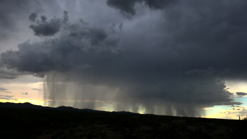 Time Lapse, Rain pours from dark clouds forming rain shafts that sweep across silhouetted landscape. 4K UHD 3840x2160