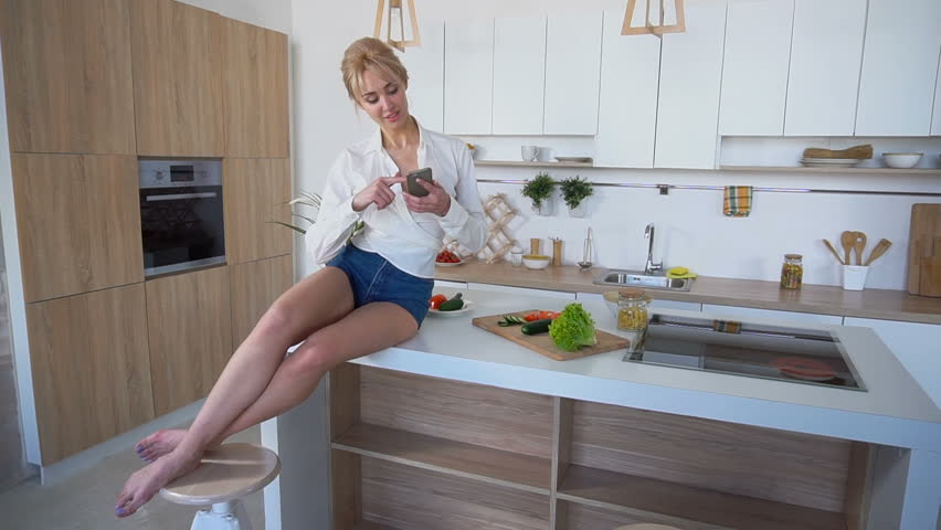 Marvelous young woman housewife holding gadget or cellphone and reading news on Internet, or looking for recipe for dinner dishes and takes piece of cucumber from cutting board that would have snack #29659678