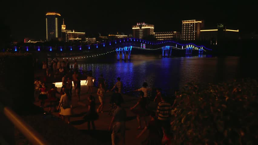 Sanya, China - April 03, 2017: Evening dances of Chinese and tourists on the embankment of the Sanya River stock footage video