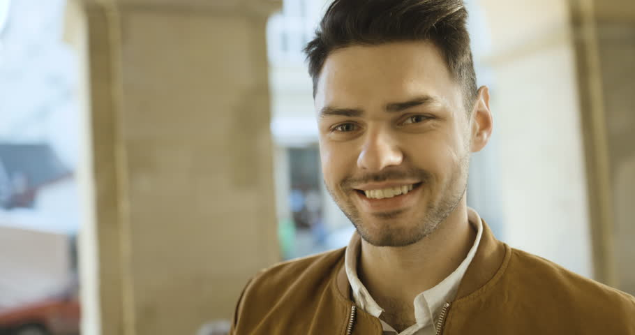 Portrait of handsome young man smiling and looking at camera at sunset on the street | Shutterstock HD Video #29721268