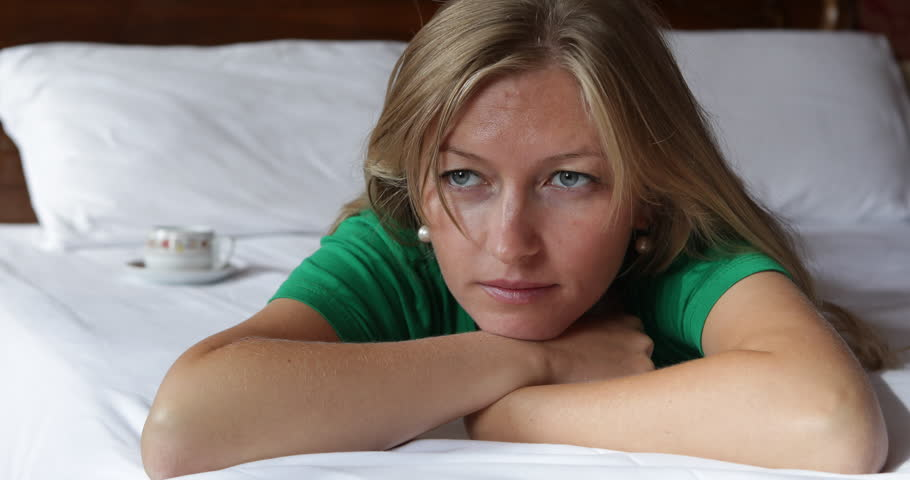 4K Unhappy woman lying in bed at home, problem financial stress, worry pensive