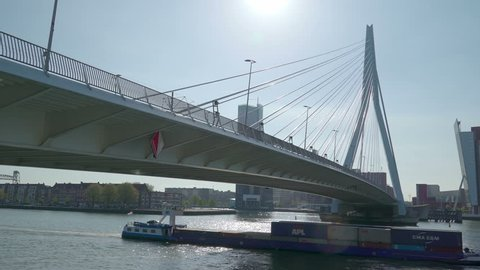 Rotterdam Netherland June 10 2017: The flat design cargo ship crossing under the bridge of Rotterdam with some cargoes on board