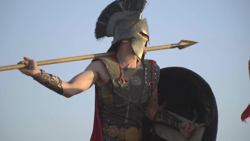 An aggressive Roman warrior beats a spear from behind his shoulder, slow motion