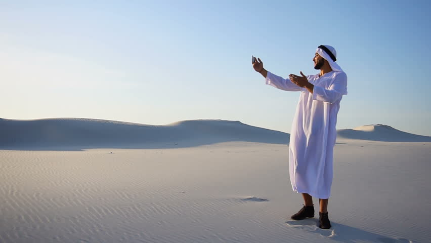 Modern handsome Muslim man Arabian Sheikh holds phone and dials friend or girl via Internet in videocall to friends or girl, chatters and smiles, looking at smartphone's screen, shows landscapes and | Shutterstock HD Video #29751073