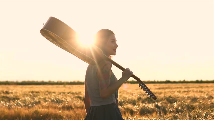 happy girl walking with a guitar at sunset field