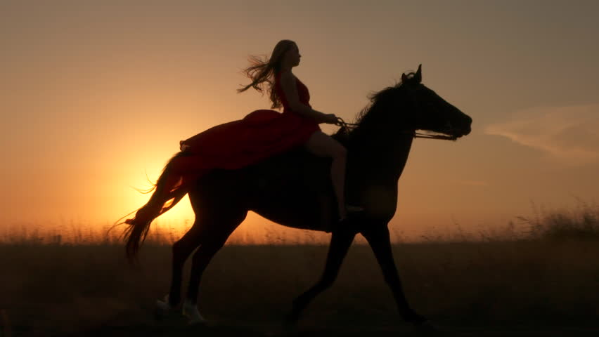Young girl in red dress riding black horse against the sun. Rider with her stallion trotting across a field at sunset. Long gown blowing in the wind. Horseback riding in slow motion.   Shutterstock HD Video #29757301