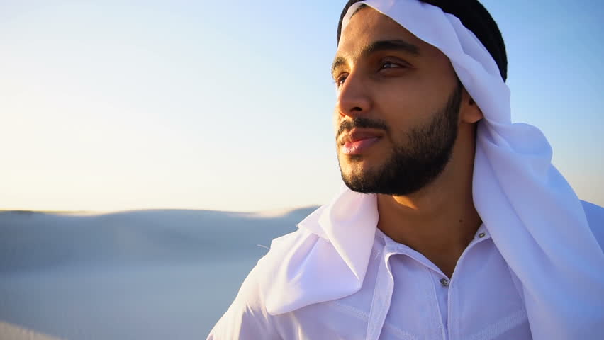 Close-up portrait of handsome Muslim young man who smiles and looks around, watching beauty of nature in sandy desert with white sand against blue sky in national suit that develops in wind. Swarthy