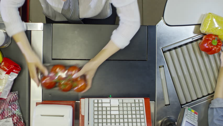 Top view of hands of female cashier scanning groceries at supermarket register in slow motion