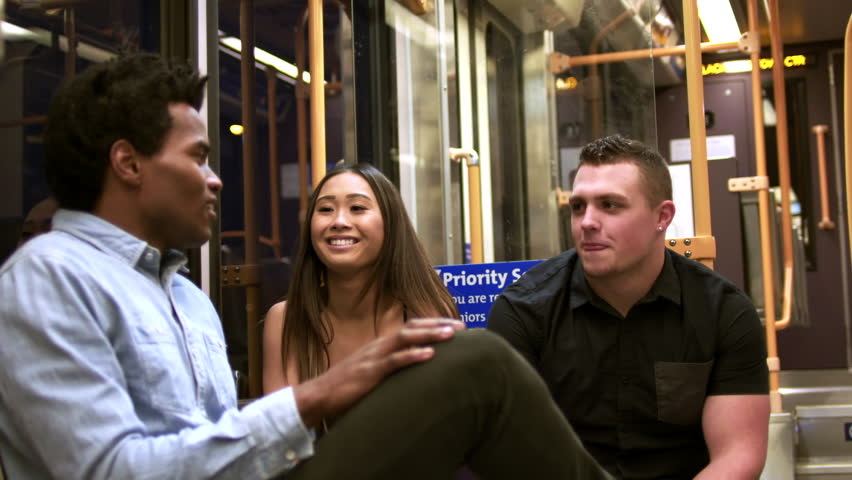 Three young adults talking and laughing while riding a train. Trouble loving teens joke around on the metro.