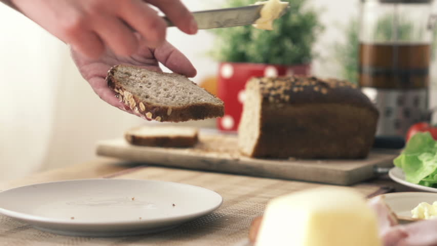 Woman spreading butter on slice of bread
