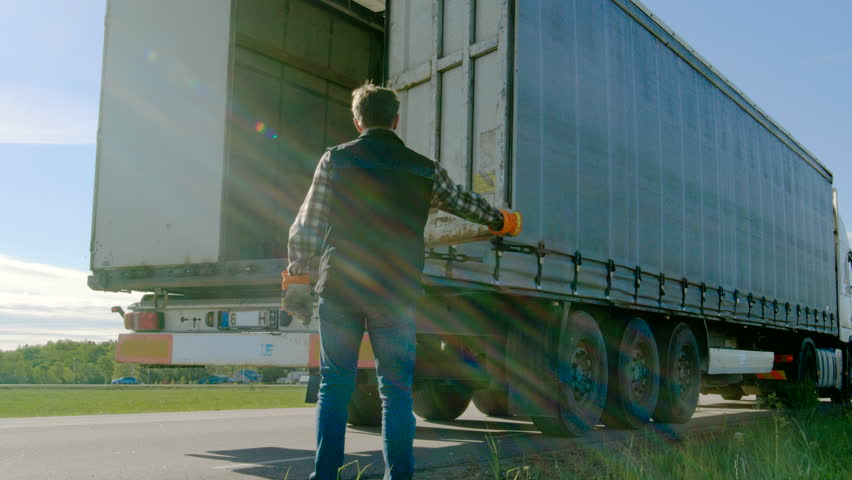 Truck Driver Closes Doors of His Parked Truck Cargo Trailer. Professional Driver Wears Heavy Duty Gloves. Shot on RED EPIC-W 8K Helium Cinema Camera.
