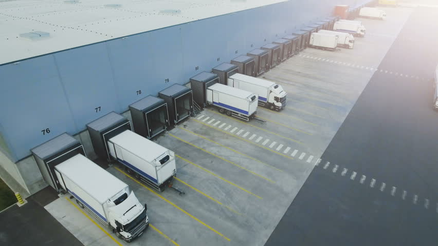 Moving Aerial Side Shot of Industrial Warehouse Loading Dock where Many Truck with Semi Trailers Load/ Unload Merchandise. Shot on Phantom 4K UHD Camera.