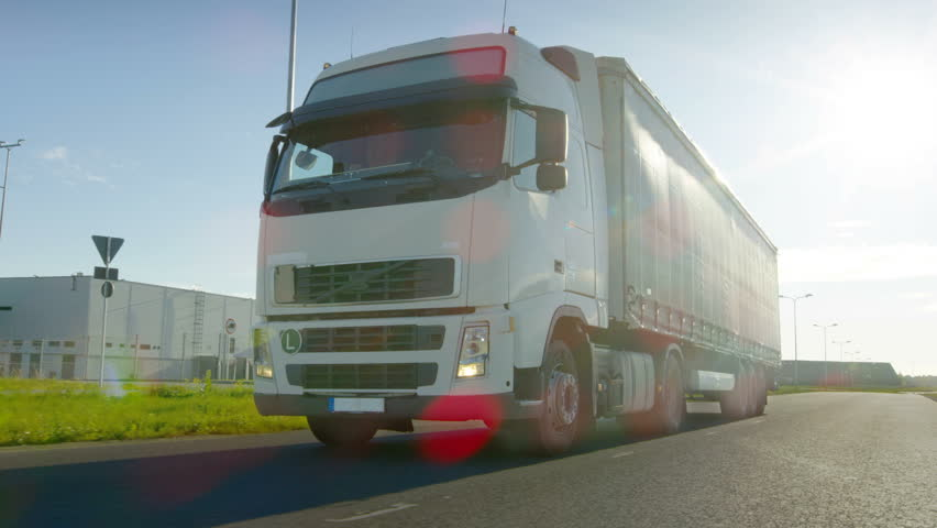 Big White Semi Truck with Cargo Trailer Moves on the Industrial Area Empty Road With Sun Shining in the Background. Shot on RED EPIC-W 8K Helium Cinema Camera. | Shutterstock HD Video #29799985