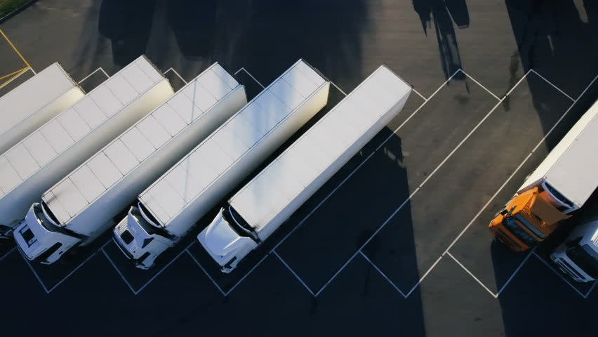 Moving Aerial Top View of Parked Semi Trucks with Cargo/ Refrigerator Trailers Standing on their Dedicated Parking Places. Shot on Phantom 4K UHD Camera.