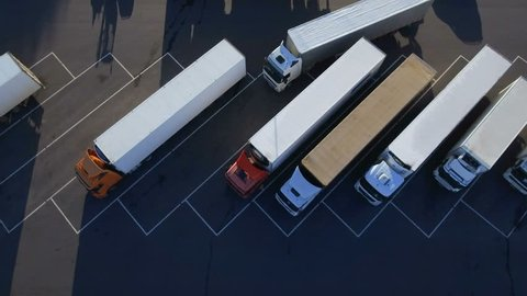 Aerial Top View of White Semi Truck with Cargo Trailer Parking with Other Vehicles on Special Parking Lot. Shot in 4K (UHD).