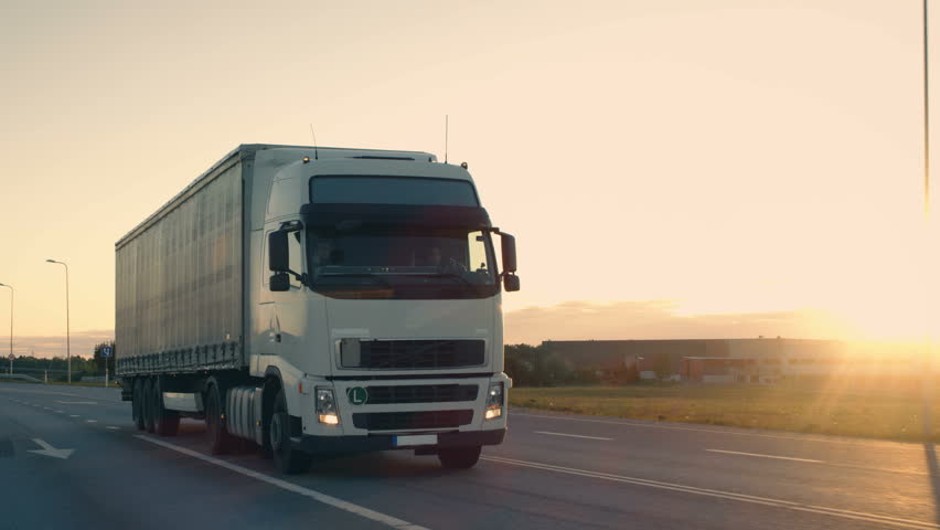 Follow-up Shot of a Semi-Truck with Cargo Trailer Moving on a Highway. White Truck Drives Through Industrial Warehouse Area in Early Hours of the Morning. Shot on RED EPIC-W 8K Helium Cinema Camera.