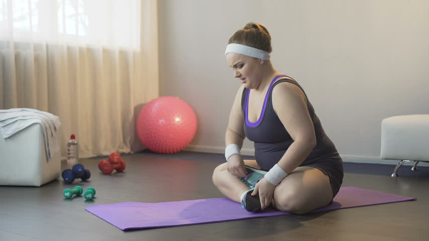 Obese girl hardly trying to take lotus position for finding peace of mind, yoga   Shutterstock HD Video #29803228