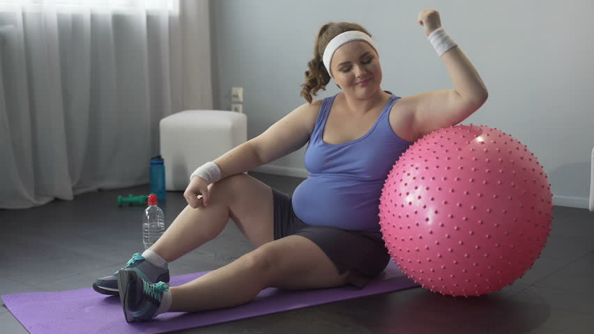 Full of strength and self-confidence, fat girl happy with successful workout